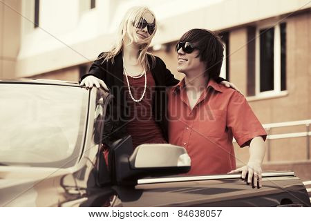 Happy young couple in a convertible car