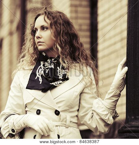 Sad beautiful fashion woman with long curly hairs in white coat