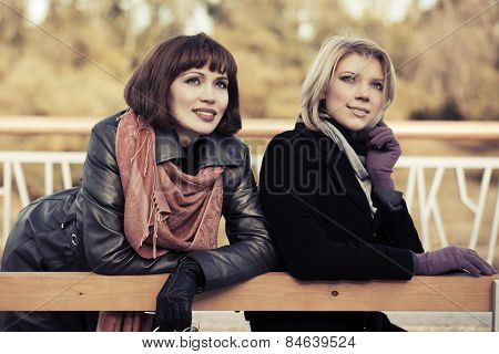 Two happy young fashion women on the bench