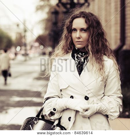 Beautiful fashion woman with long curly hairs in white coat