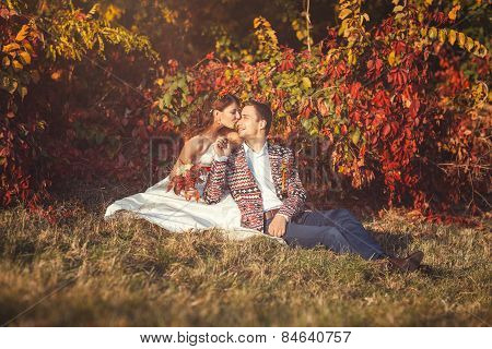 Newlyweds Embracing Sitting On Grass Near The Tree