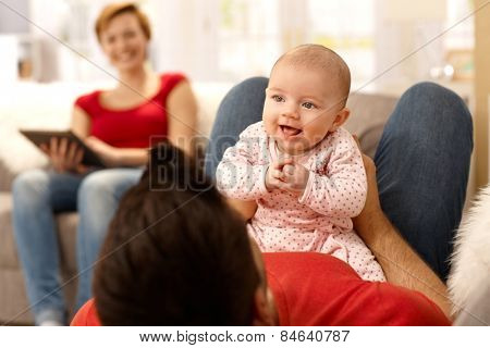 Baby girl and father playing on sofa, mother watching from background.