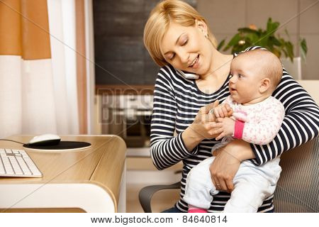 Young woman talking on mobile holding baby on lap.