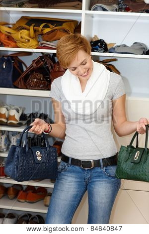 Young woman standing front of open wardrobe, hesitating which bag to take.