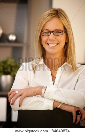 Closeup portrait of happy blonde businesswoman smiling, looking at camera.