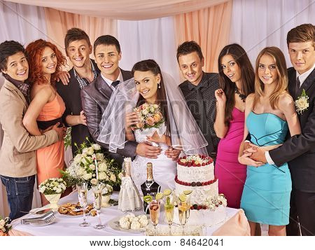 Group people at wedding table with cake. Bride in a veil