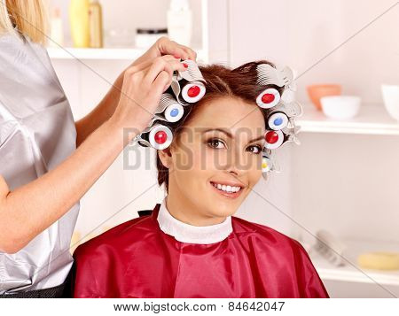 Happy woman wear hair curlers on head. Barber is in  barbershop