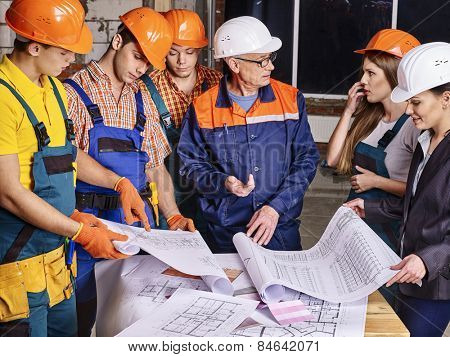 Business group people in builder helmet indoor. Drawings on table