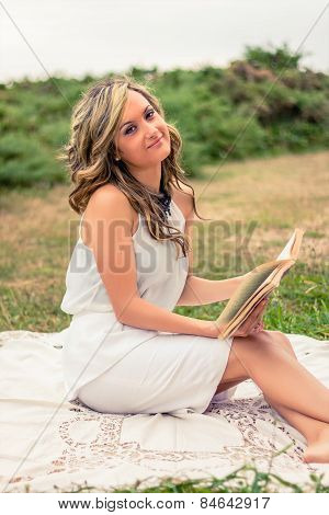 Romantic girl reading a book sitting outdoors