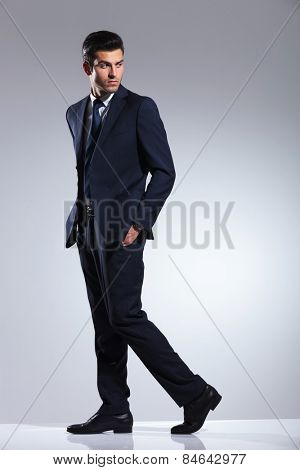 Side view picture of a young business man walking on grey studio background with his hands in pockets.