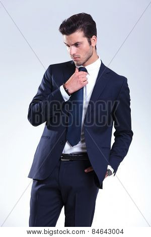 Portrait of a young elegant business man fixing his tie while looking down.