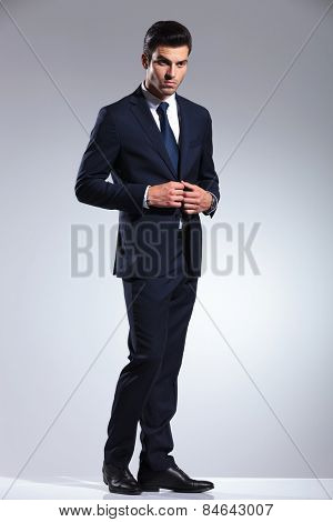 Side view picture of a handsome business man closing his jacket while looking away from the camera.