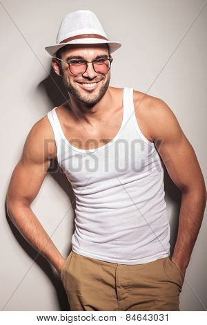 Smiling young fashion man leaning on a white wall holding both hands in his pocket.