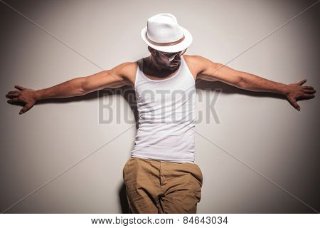 Sexy young casual man leaning on a white wall with his arms open, looking down.