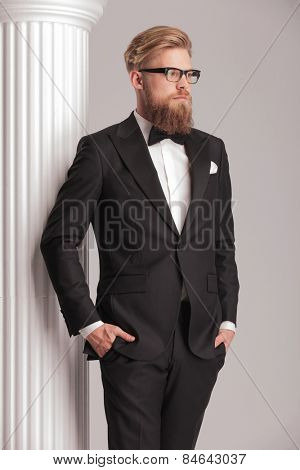 Side view picture of a elegant young man wearing a tuxedo. He is posing near a white column holding both hands in his pockets.