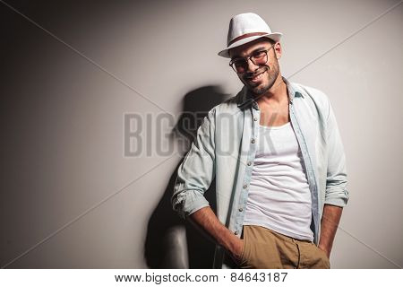 Smiling young fashion man looking at the camera while holding his hands in pockets.