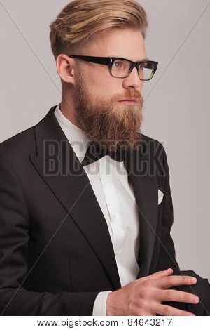Close up picture of a young business man holding his hand on the knee while sitting, looking away from the camera.