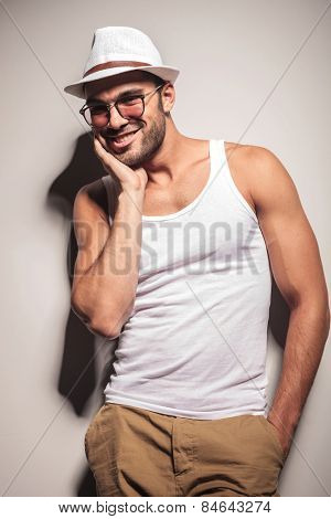 Happy young casual man leaning on a white wall with one hand in his pocket while holding the other hand on his cheek.
