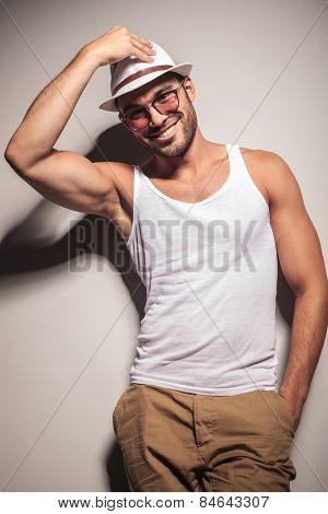 Happy young fashion man smiling to the camera while fixing his hat and holding one hand in his pocket.