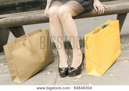 Shopping woman sit and rest in Xinyi district, the business and commercial center in Taipei, Taiwan, Asia. Closeup image focus on foot.