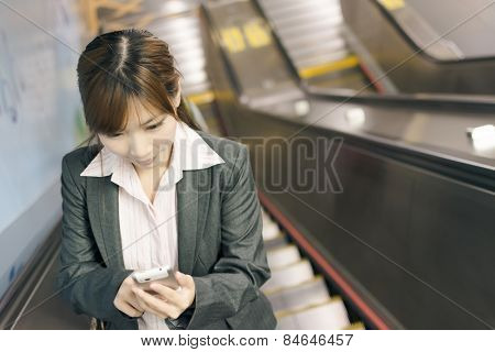 Asian young business woman stand on escalator use cellphone in the MRT station, shot at Xinyi business district, Taipei, Taiwan.