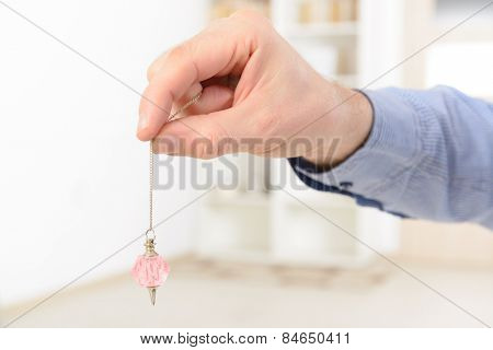 Hand with pink crystal pendulum, tool for dowsing.