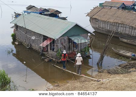 People go to the floating house at Tonle Sap lake shore, Cambodia.