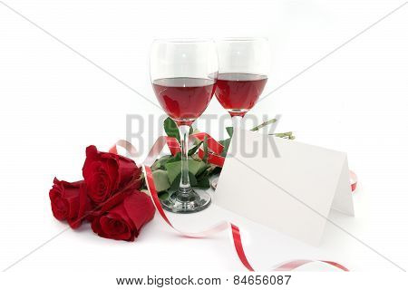 Wine In Glasses, Red Roses, Ribbon And Empty Card For A Message, Isolated On White Background.