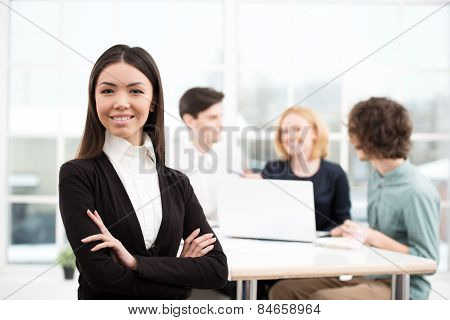 Businesswoman looking at camera with her business team on background