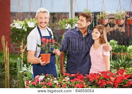 Smiling couple and a gardener in a nursery shop between plants and flowers