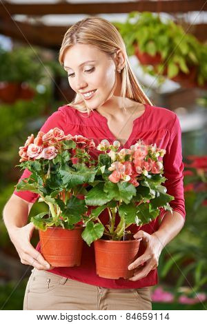 Smiling woman holding two begonia flowers in garden center