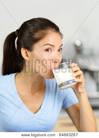 Almond milk woman drinking lactose-free beverage. Young Asian adult sipping a glass of organic soy based or nut milk drink as a dairy substitute for a vegan diet.