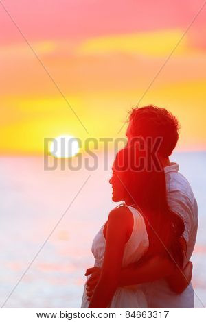 Couple watching romantic sunset during beach holidays. Newlyweds in a happy relationship at sunset during travel holidays vacation getaway. Interracial couple, Asian woman, Caucasian man.