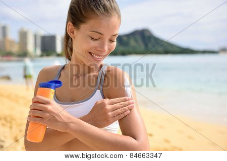 Sunscreen fitness woman applying suntan lotion. Sporty Beautiful happy asian woman with suntan cream applying sun protection before fitness running on beach during summer. Waikiki, Oahu, Hawaii.