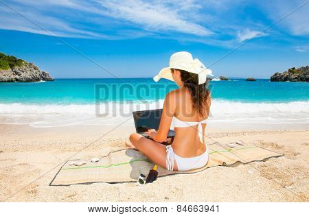 Beautiful woman with laptop computer in sunhat  enjoying on beach. Greece.