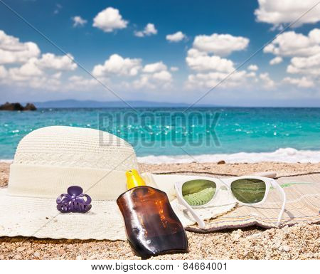 Sunglasses , sunsunhat, suncream on beach. Greece.