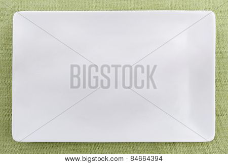 Empty plate on green tablecloth