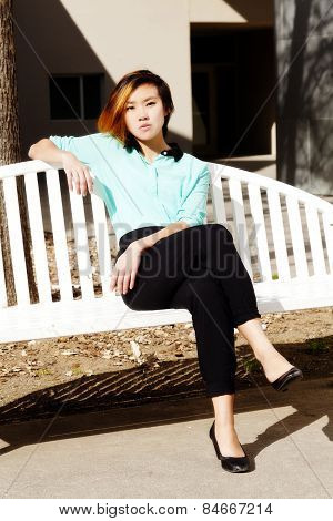 Young Asian American Woman Sitting On Bench