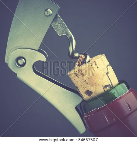 Opening of wine bottle by corckscrew. Retro style filtred image