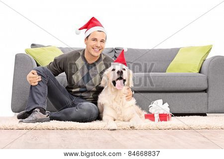 Man and a dog with Santa hats sitting by a sofa isolated on white background