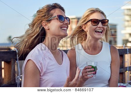 Happy young women chatting laughing outdoor on rooftop terrace