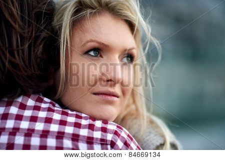 Nostalgic woman hugging her husband in the windy outdoors