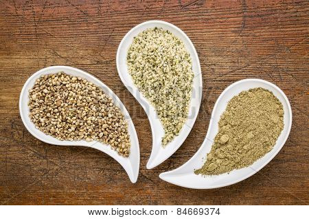 hemp seeds, hearts and protein powder in teardrop shaped bowls against grunge wood