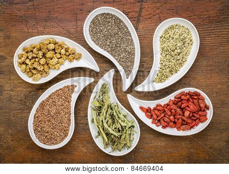 superfood samples  (mulberry, chia seeds, hemp seeds, goji berry, stevia leaf, flax seed) in teardrop shaped bowls against grunge wood