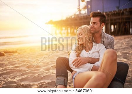 romantic couple having fun at santa monica on beach with bright warm lens flare and image filter