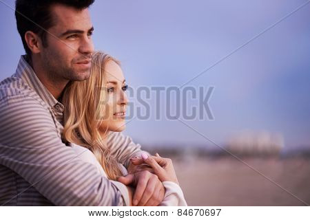 couple on beach at twilight looking outwards with shallow depth of field