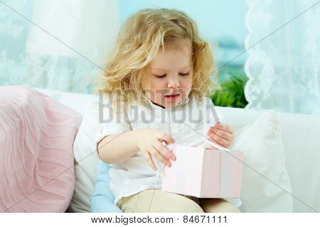 Cute little girl unpacking her gift