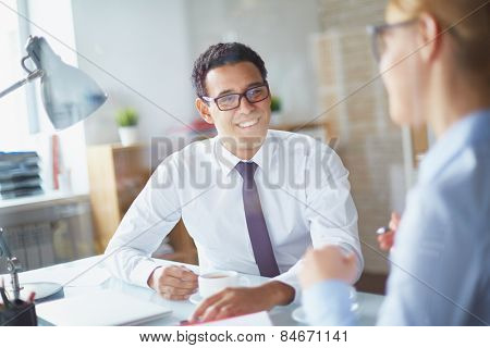 Happy businessman listening to his partner at coffee break