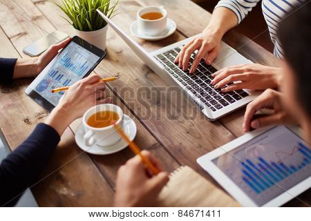 Hands of businesspeople during work with information technologies