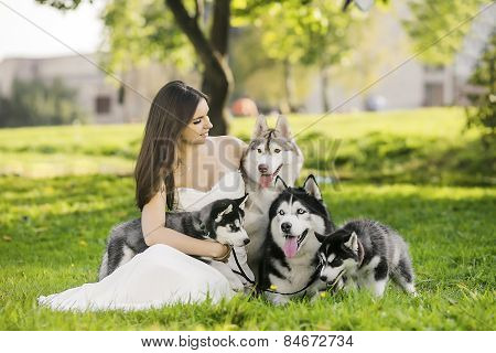 .the Girl In The White Dress Smiles. Sitting On The Grass And Looks At The Family Of Husky Dogs. Sum